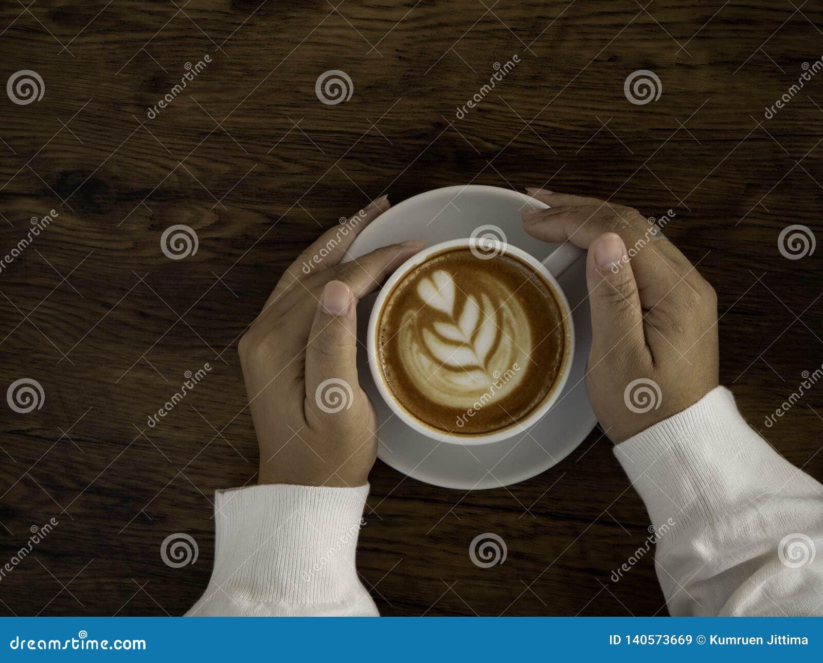 Kaffee Latte mit schöner Lattekunst an Hand