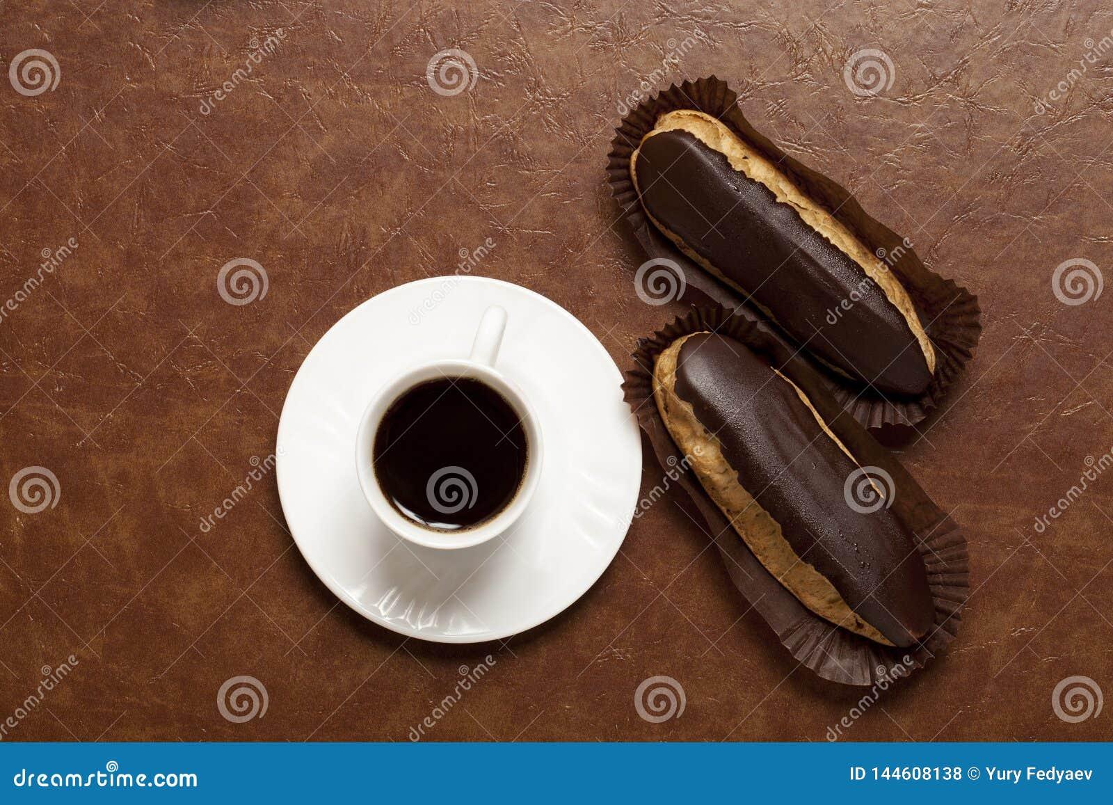 Kaffee, Schokolade Eclair, Kaffee in einer weißen Schale, weiße Untertasse, auf einer braunen Tabelle, Eclair auf Papierstand
