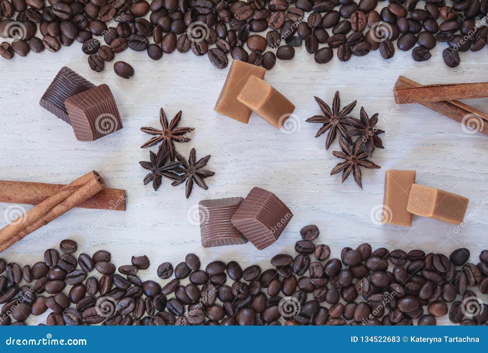 Kaffeebohnehintergrund mit Schokolade, Anis, Karamell und Zimt