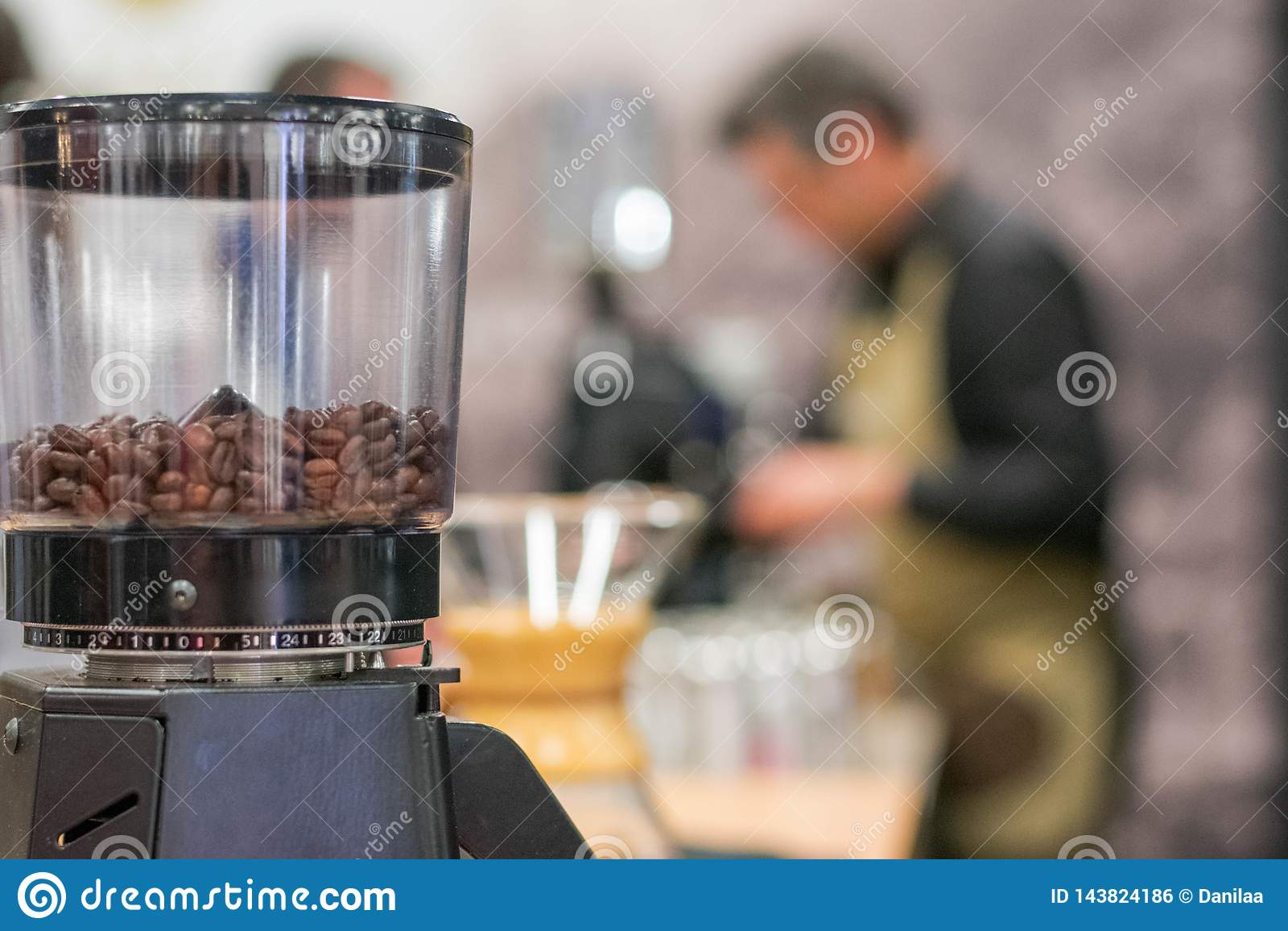 Kaffeemühle mit unscharfem Kellner im Hintergrund