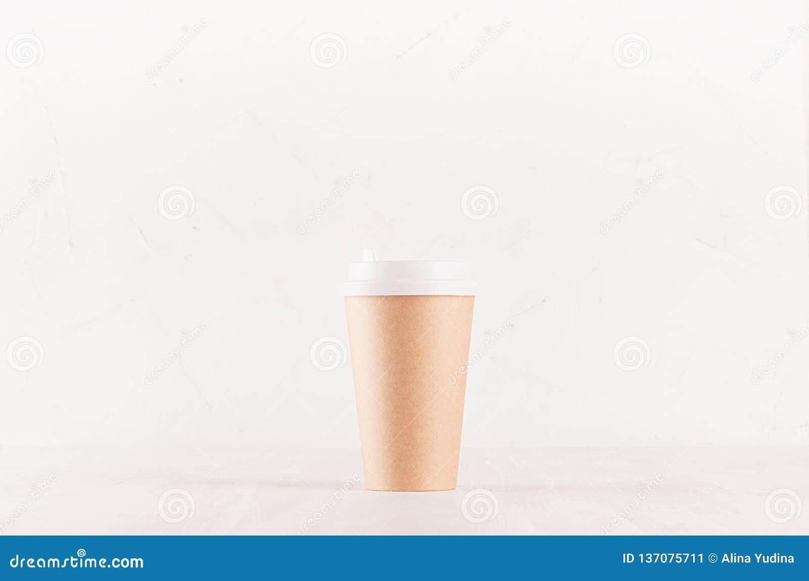 Kaffeemballagemodell - kraft brun pappers- kopp med det vita locket på det vita träbrädet, coffee shopinre