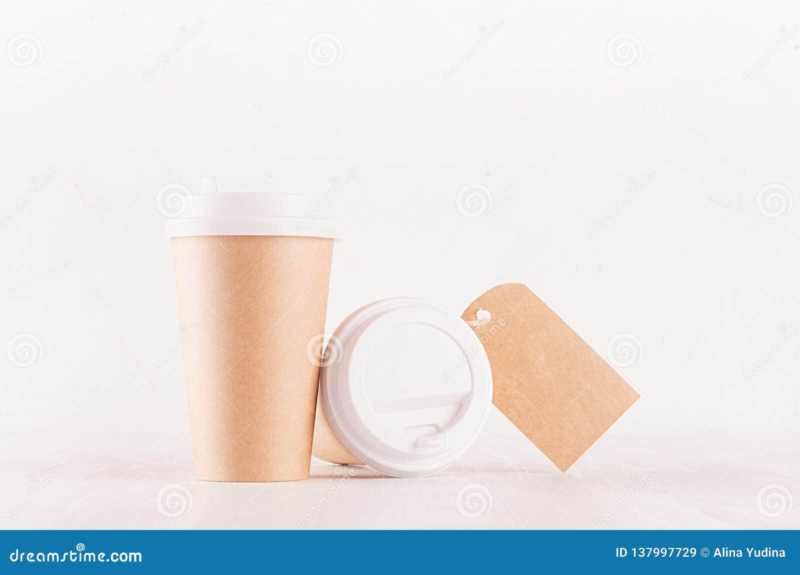 Kaffeemballagemodell - kraft bruna pappers- koppar, tomt vitt lock och etikett på det vita träbrädet, coffee shopinre
