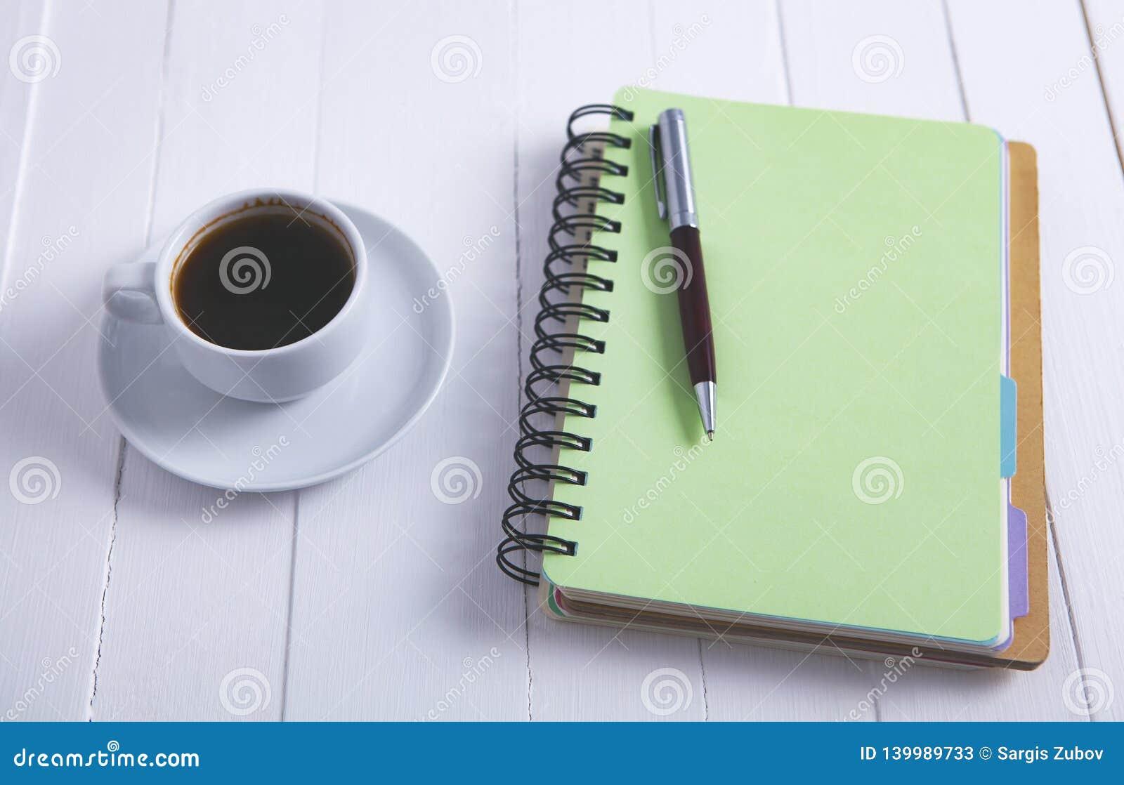 Kaffeenotizbuchstift auf hölzernem Hintergrund