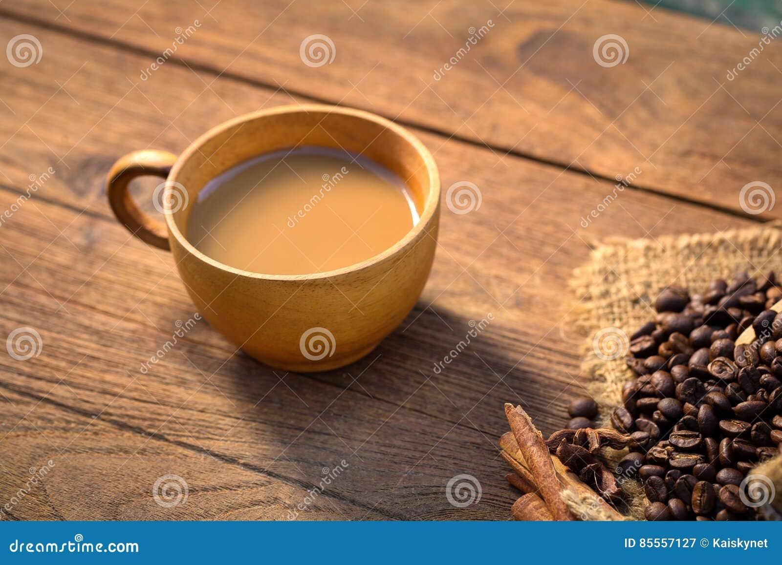 Kaffeetasse und Kaffeebohnen auf hölzernem Hintergrund