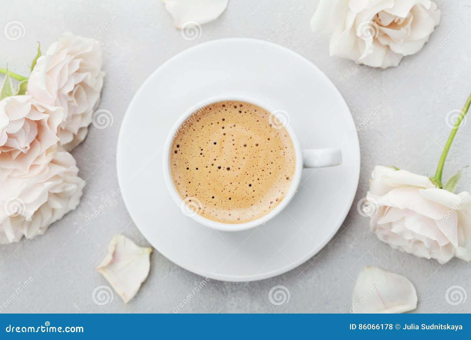 Kaffeetasse und rosafarbene Blumen der Weinlese für guten Morgen auf grauer Steintischplatteansicht in Ebene legen Art Schönes Fr