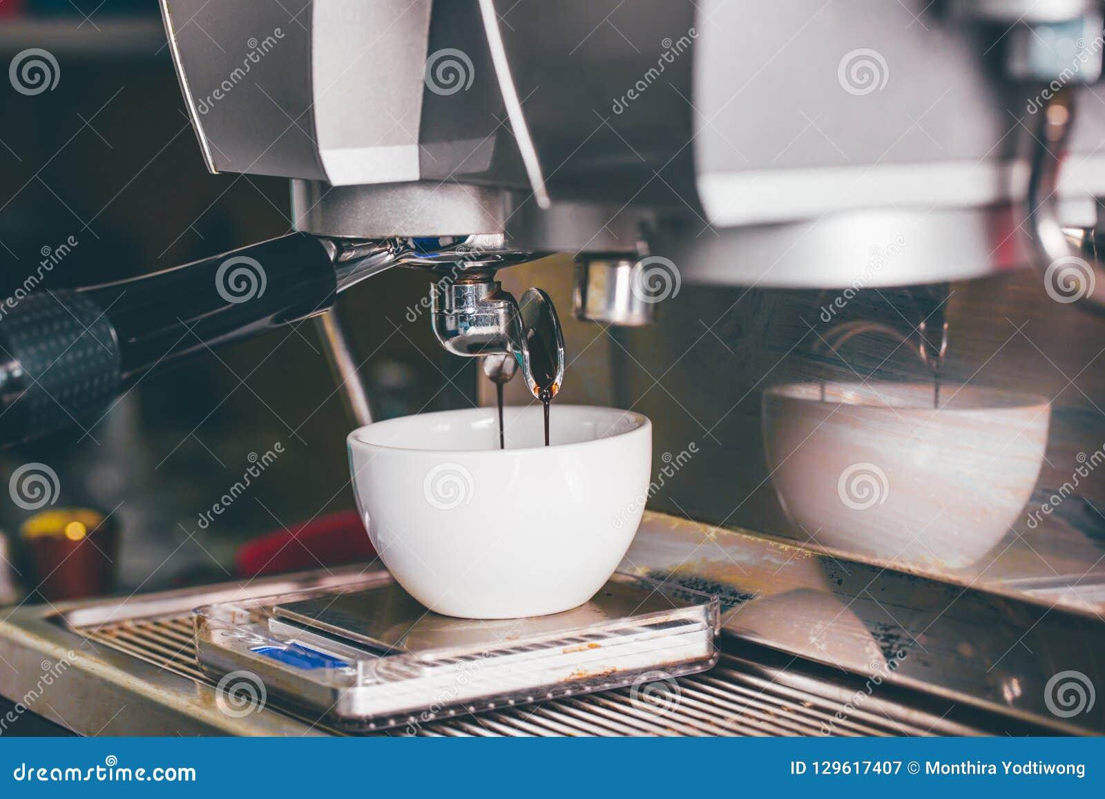 Kaffeextraktion som häller in i en kopp från yrkesmässig kaffemor
