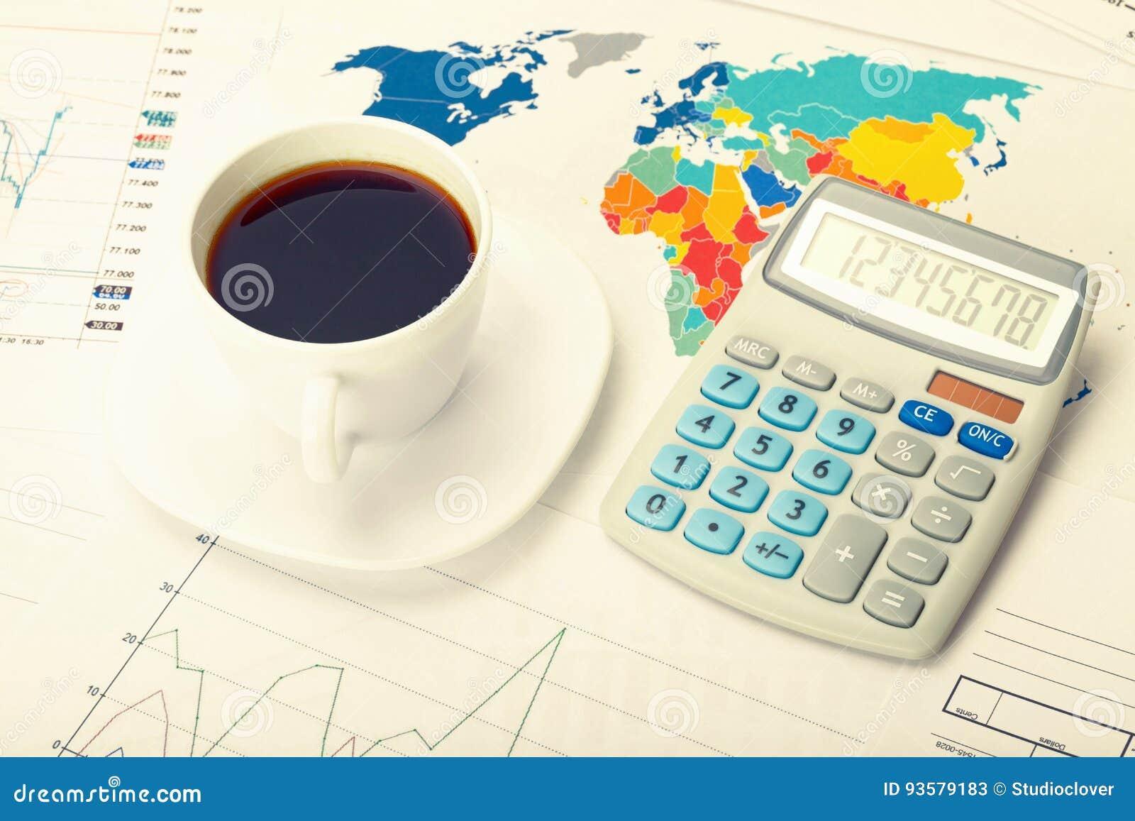 Kaffekopp och räknemaskin över världskarta och några finansiella diagram Filtrerad bild: kors bearbetad tappningeffekt