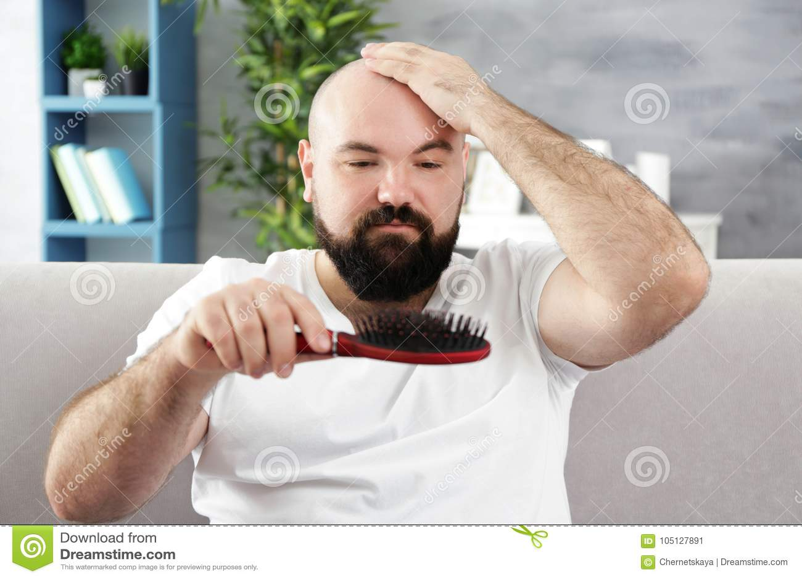 Kahler erwachsener Mann mit Haarbürste