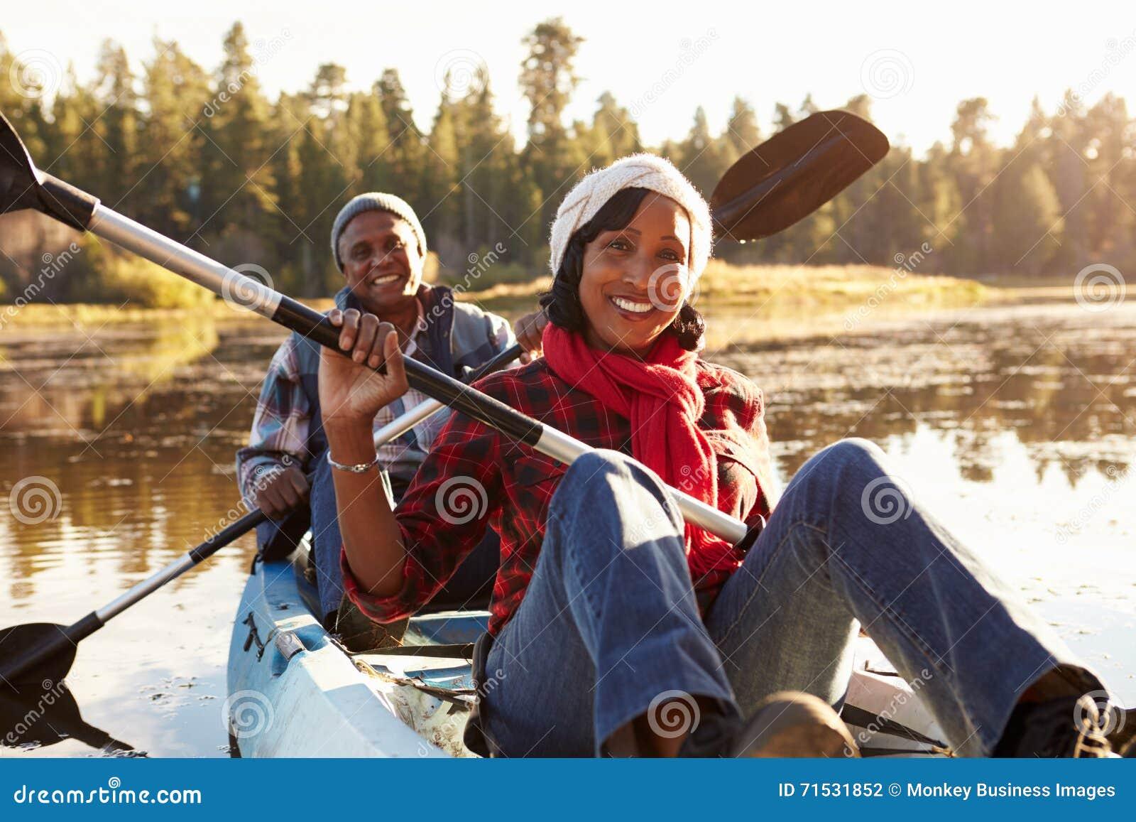 Kajak afroamericano mayor del rowing de los pares en el lago