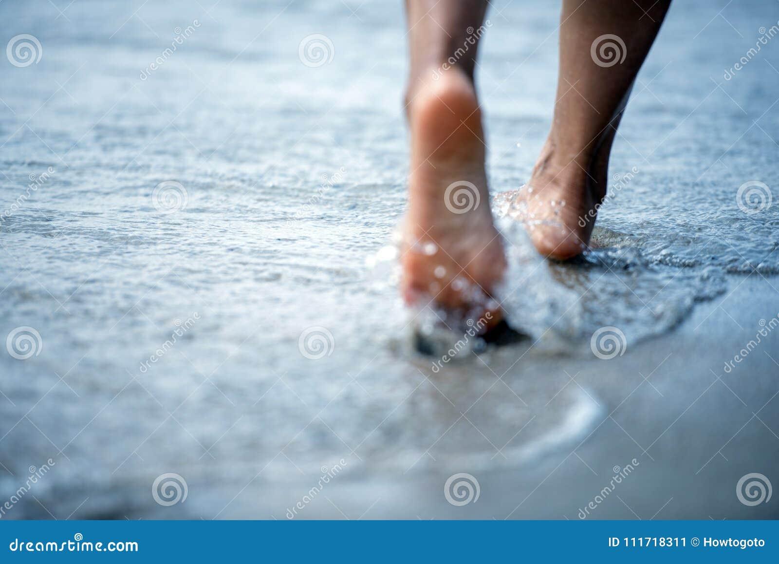 Kal fot för kvinna som går på sommarstranden övre ben för slut av den unga kvinnan som promenerar vågen av havsvatten och sand på