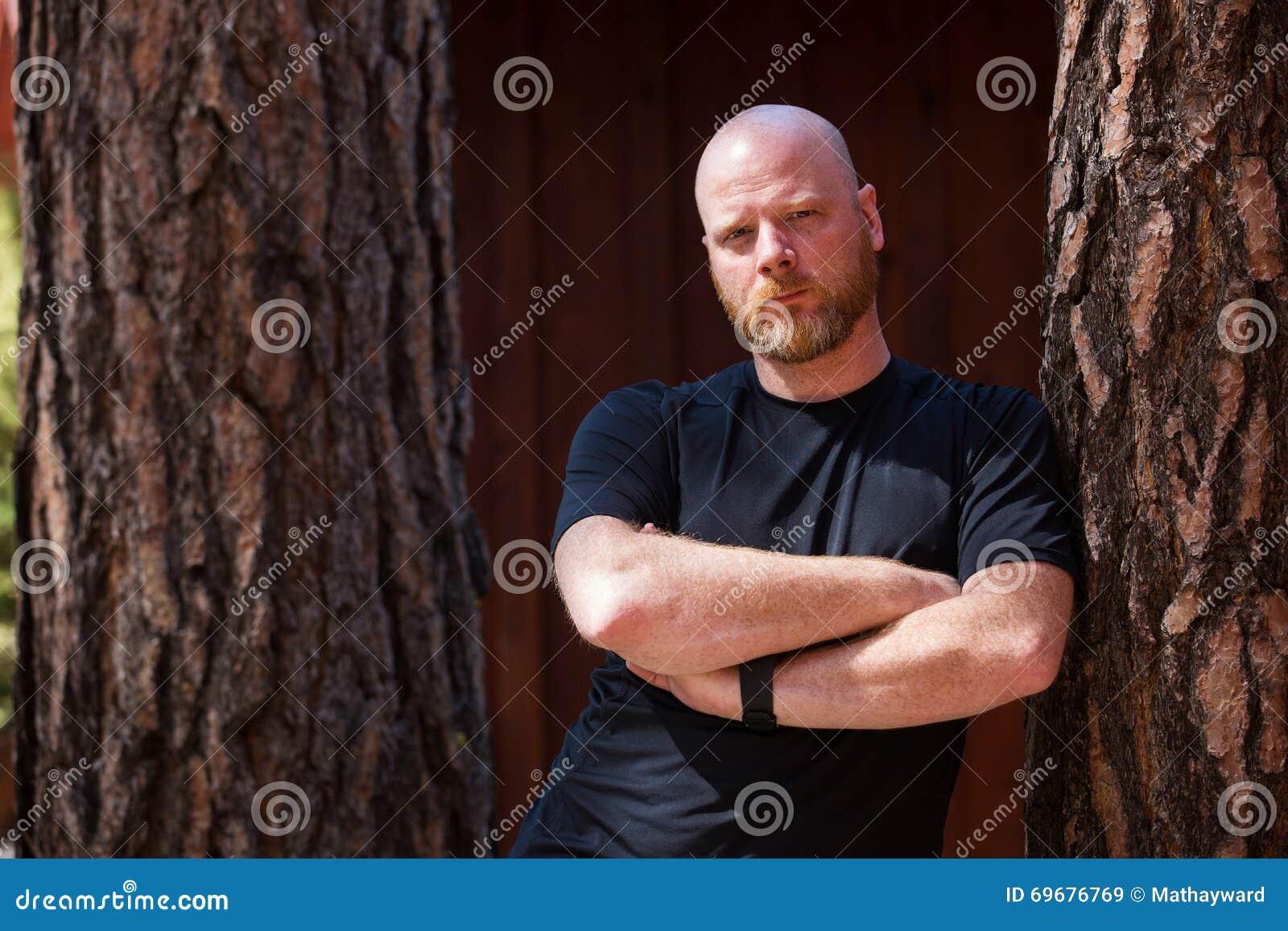 Kale mens met een baard en gekruiste wapens