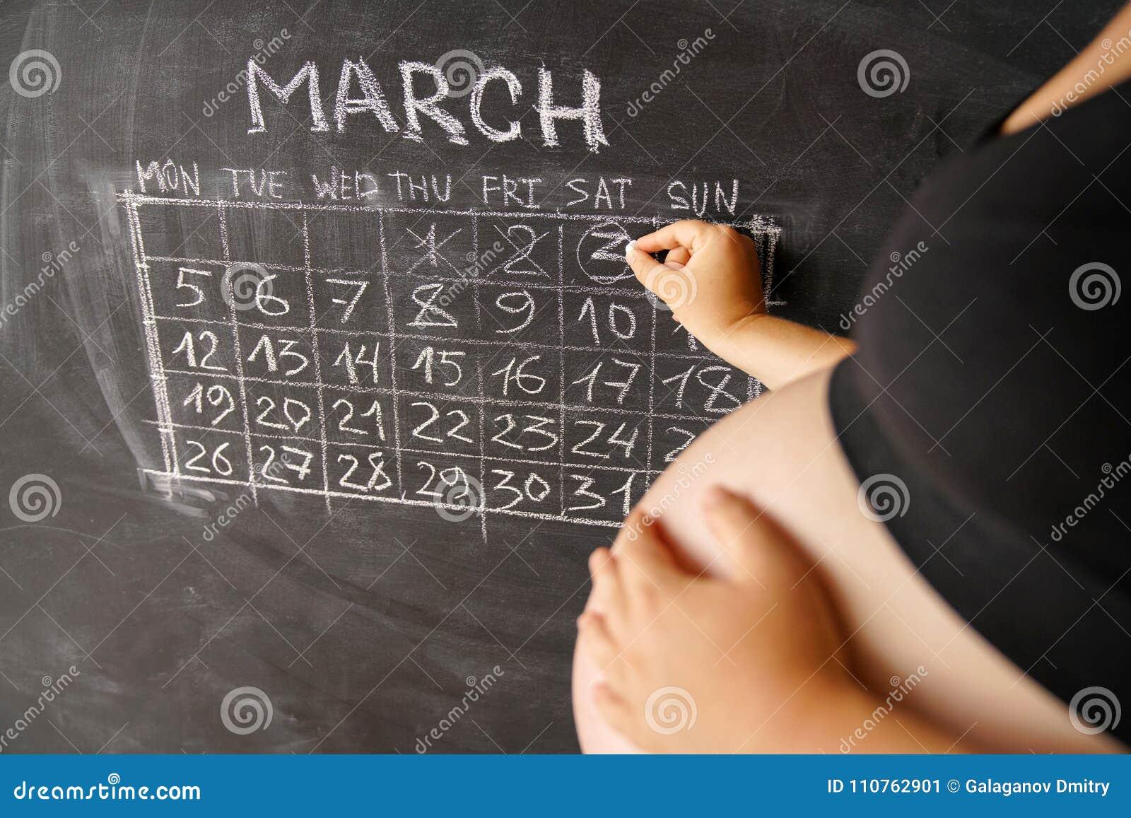 Kalendarz kobieta w ciąży miesiąca Marzec odliczający dni z kalendarzem dla narodziny dziecko na chalkboard przeciw jako tła popa