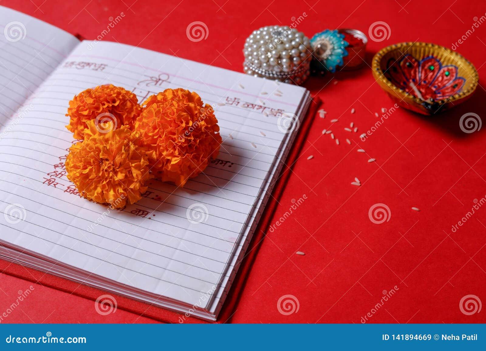 Kaligrafia pisze w hindi Shubha Labh znaczy dobroć & bogactwo, nad Czerwonej księgowości nutową książką, diya,