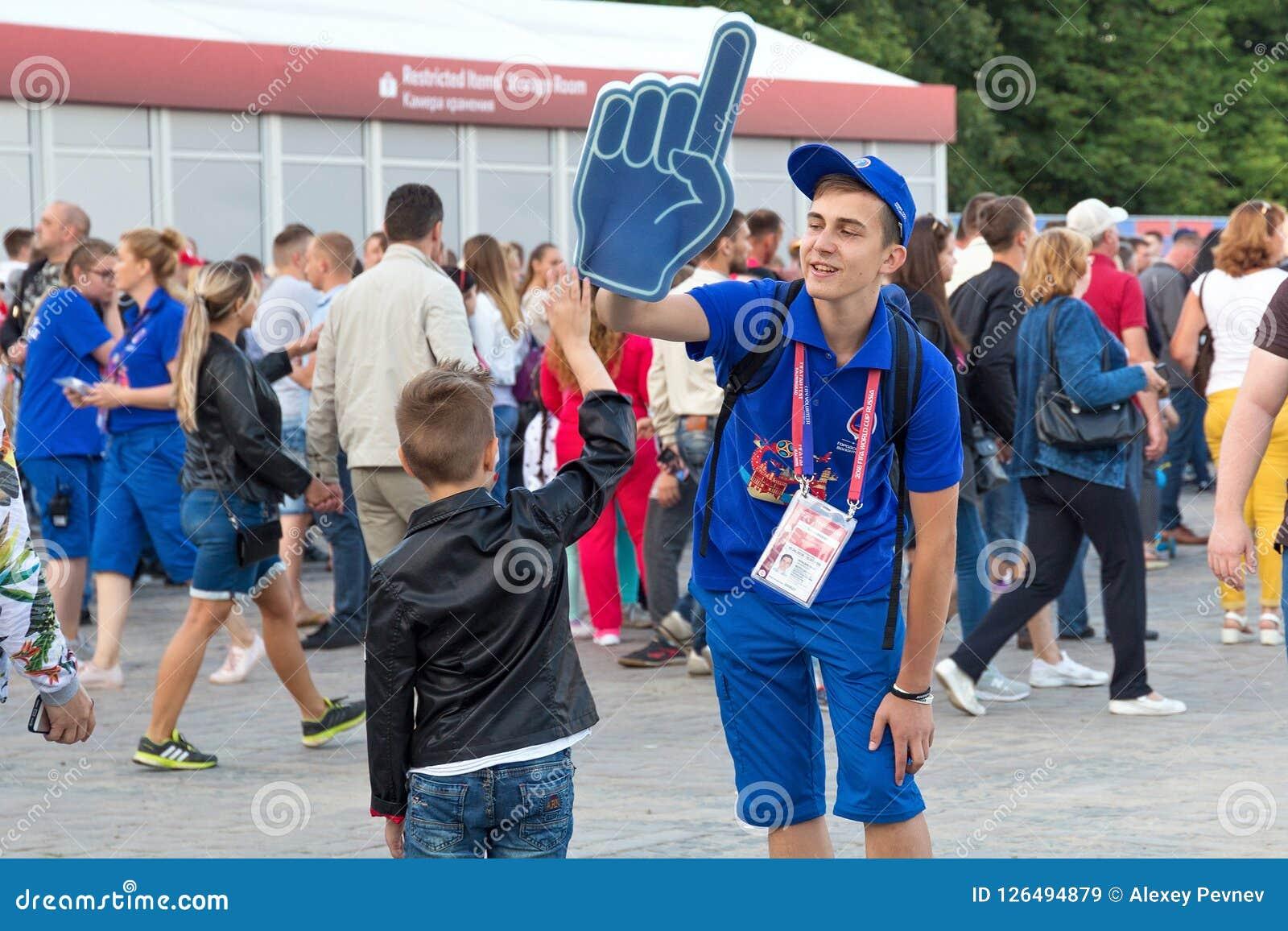 KALININGRAD, RÚSSIA - 16 DE JUNHO DE 2018: Voluntários novos na zona do Fest do fã de Kaliningrad FIFA