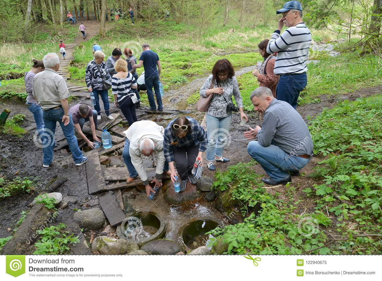 KALININGRAD REGION, RUSSIA. Tourists gather water from the spring on the river bank Blue