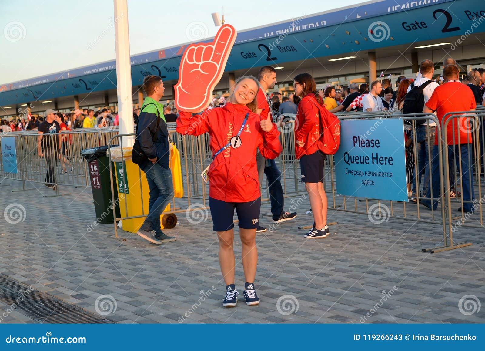 Kaliningrad, Russland Der Mädchenfreiwillige vor dem hintergrund des Eingangsanschlusses des baltischen Arenastadions Das FIFA-We