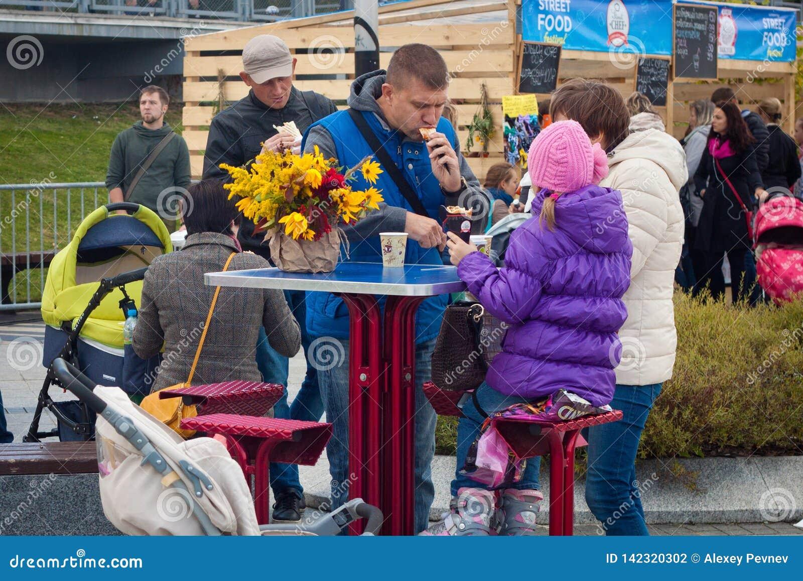KALININGRAD, RUSSLAND - 9. SEPTEMBER 2014: Unbekannte Familie, die hat, nahe dem Straßennahrungsmittelcafé zu Mittag zu essen in