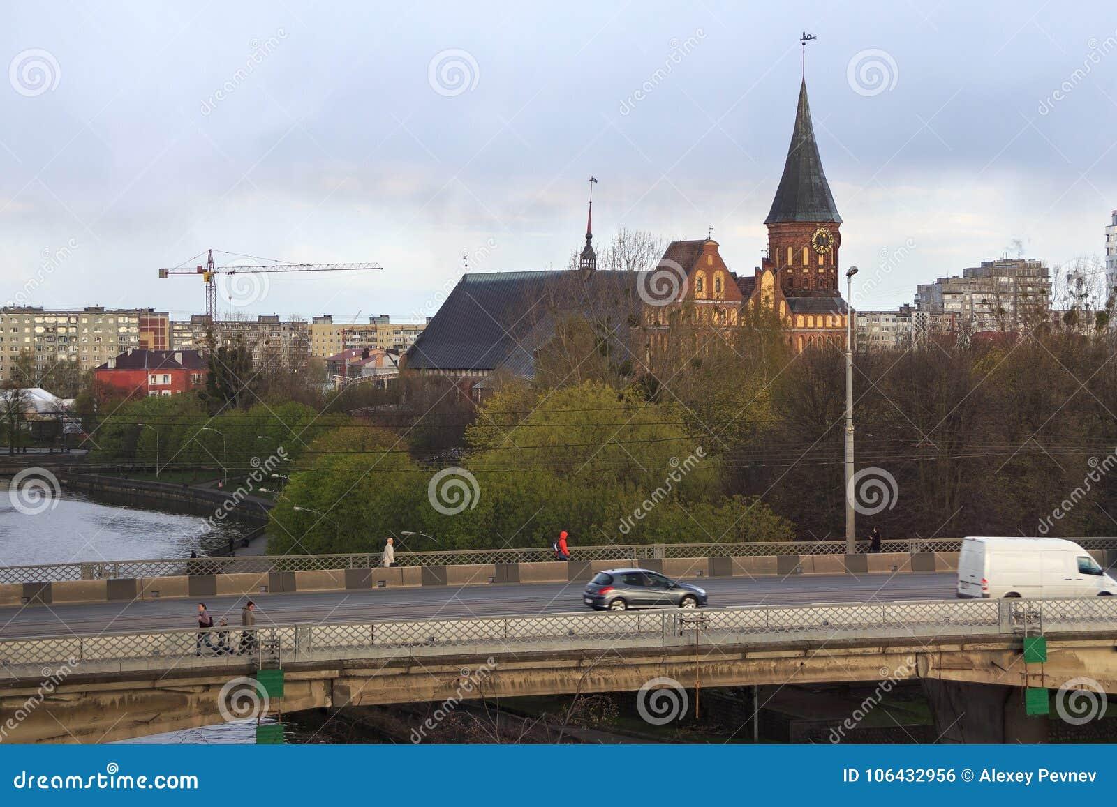 KALININGRAD RYSSLAND - APRIL 25, 2016: Sikt av den gotiska Konigsberg domkyrkan och planskild korsningbron över den Pregolya flod