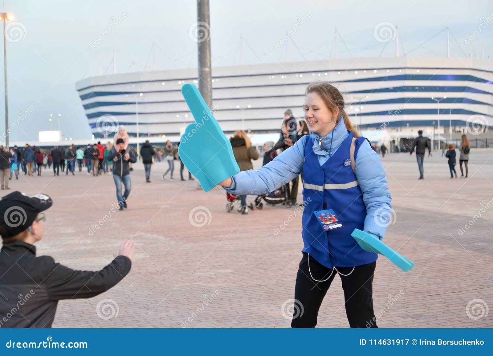 Kaliningrad Ryssland Volontären av den FIFA världscupen av 2018 med indexet på en hand baltisk stadion för arena