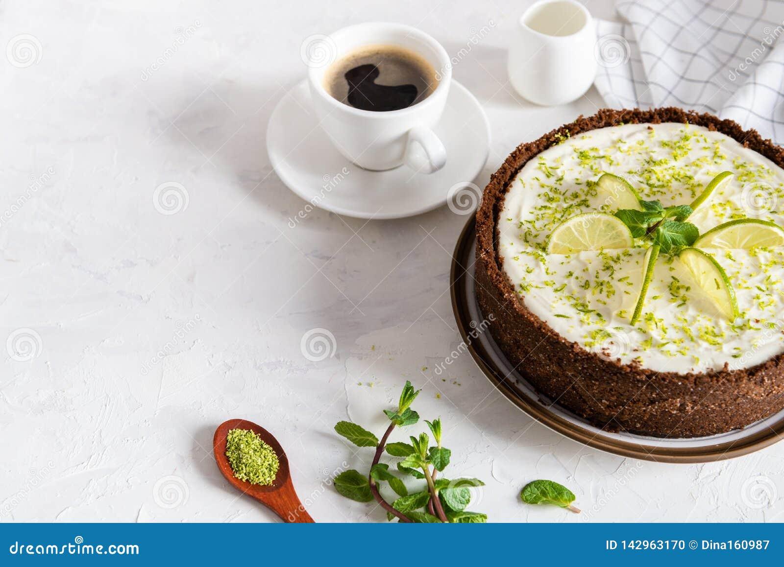 Kalkk?sekuchen mit Pfefferminz K?sekuchen mit Tasse Kaffee auf wei?em Hintergrund Weicher Fokus Kaffeehaus, S??igkeitenkonzept