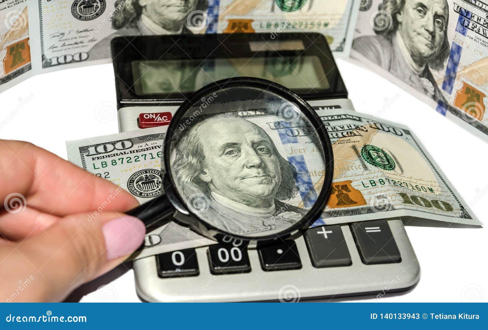Kalkulator, amerykańscy dolary, magnifier i żeńska ręka na białym tle,
