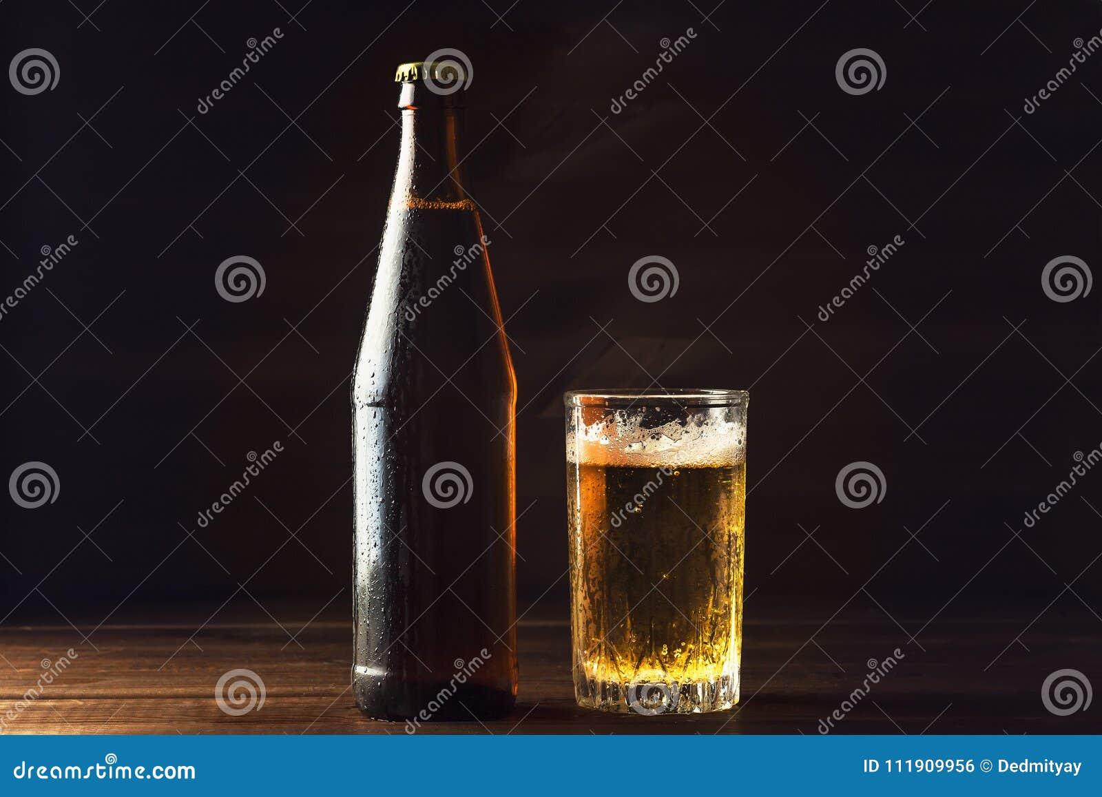 Kall ölflaska och exponeringsglas med nytt öl i droppar av vatten på mörk bakgrund, hantverkbryggeri