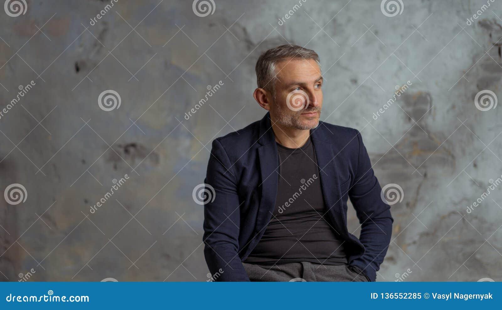 Kall affärsman med grått hår och skägg som sitter på grå bakgrund