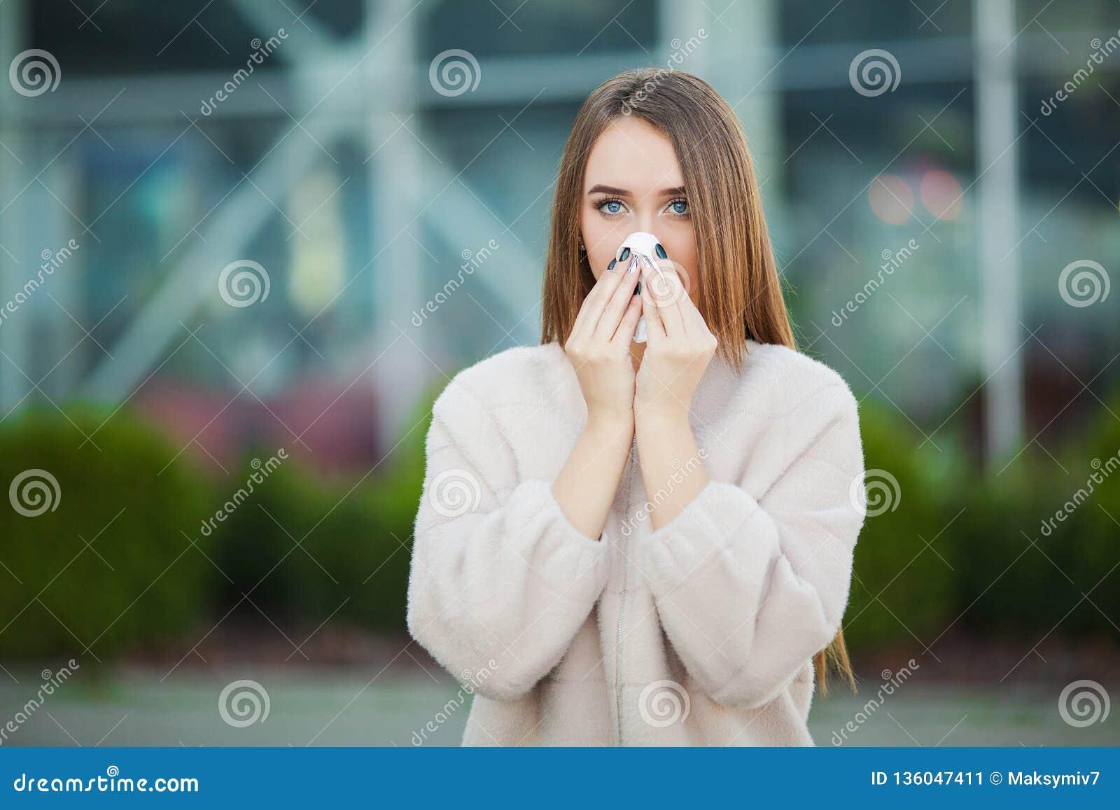 Kall influensa Den unga attraktiva flickan, fångade en förkylning på gatan, torkar hennes näsa med en servett