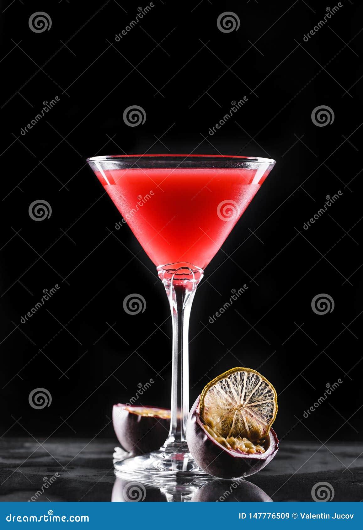 Kall röd coctail med passionfrukt i högväxt exponeringsglas på svart bakgrund Sommardrinkar och alkoholiserade coctailar