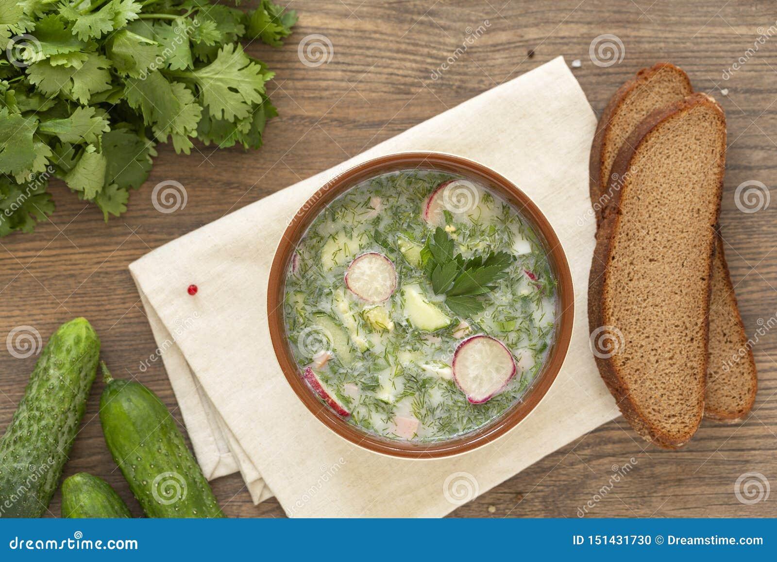 Kall soppa för sommaryoghurt med rädisan, gurkan och dill på trätabellen Rysk kall grönsaksoppa på yoghurt