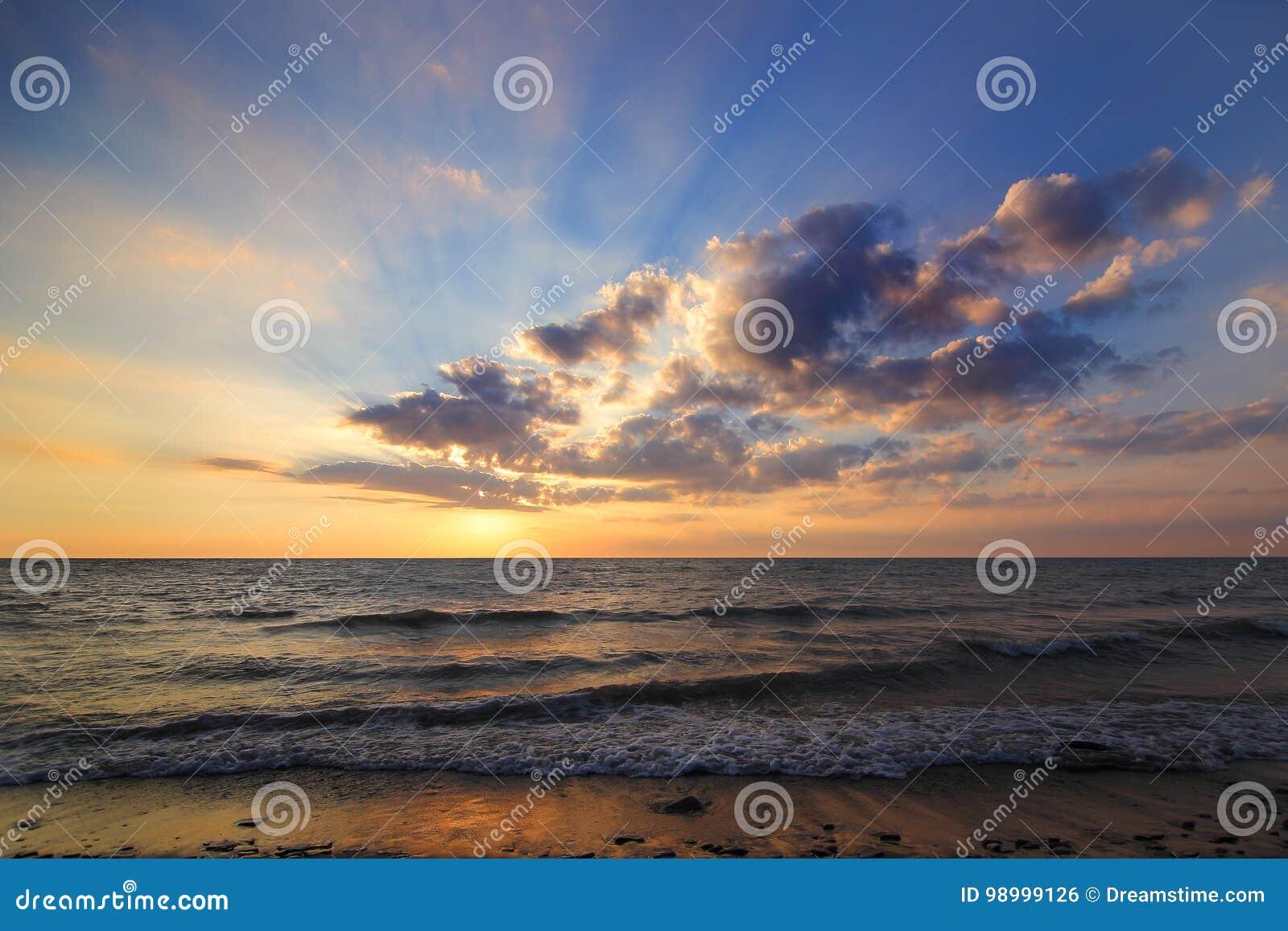 Kall strandsolnedgång som är varm och