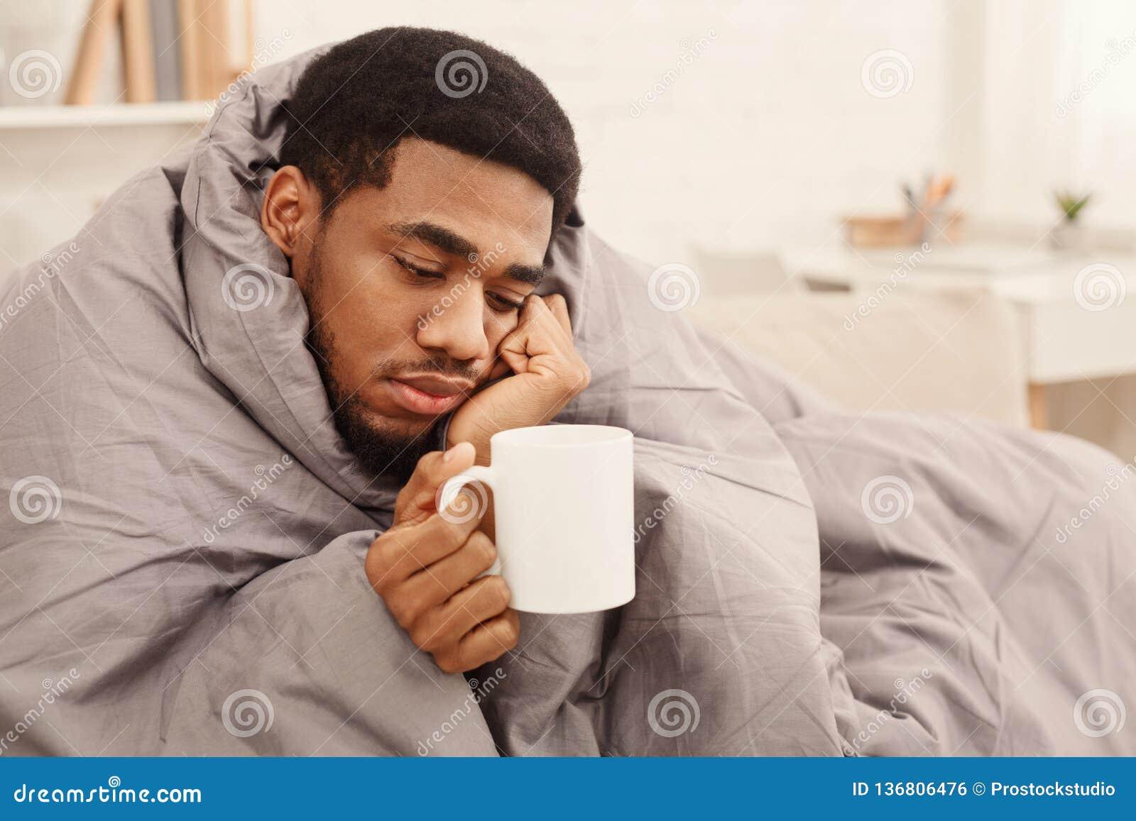 Kall svart man med influensa som slås in i varm filt