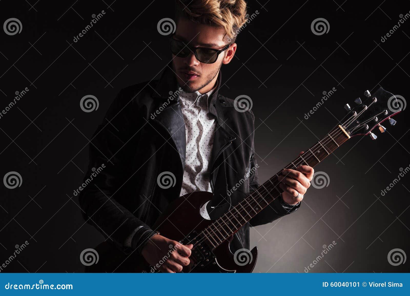 Kall ung gitarrist som spelar hans elektriska gitarr