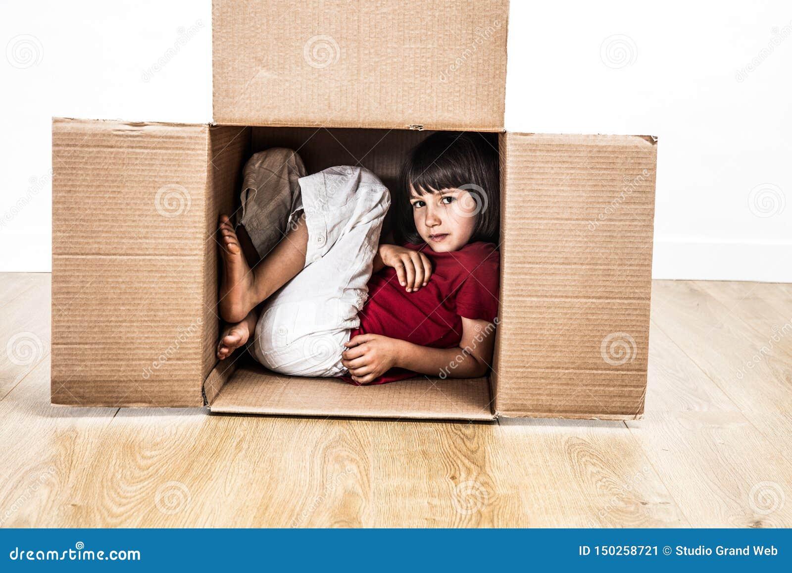 Kallt barn som krökas i kartongen som döljer i litet hus