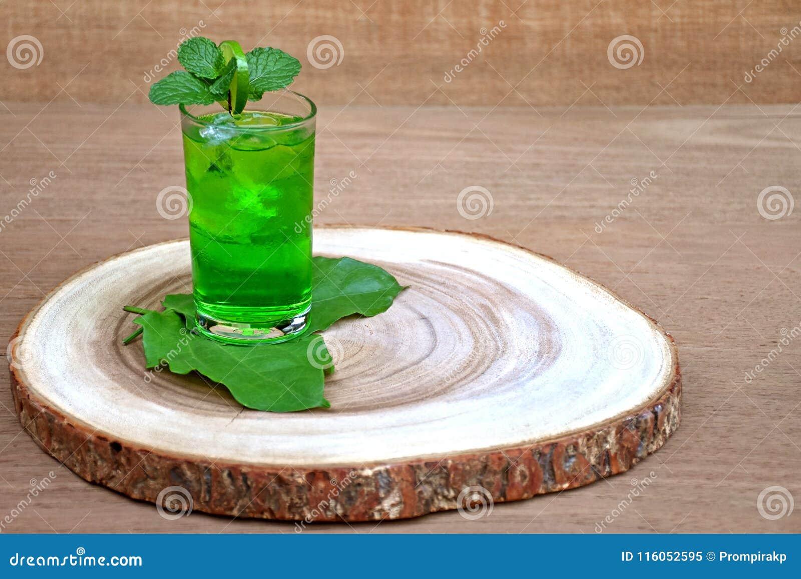 Kallt och uppfriskande limefrukt- och mintkaramellgräsplanvatten i ett exponeringsglas på trä