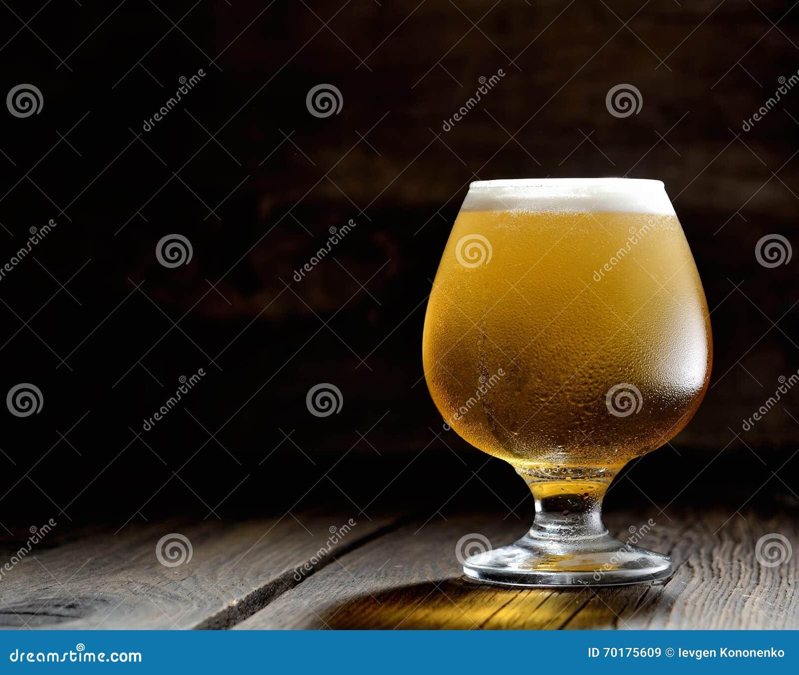 Kallt skummigt öl i ett exponeringsglas av original- färg på a på en träbakgrund