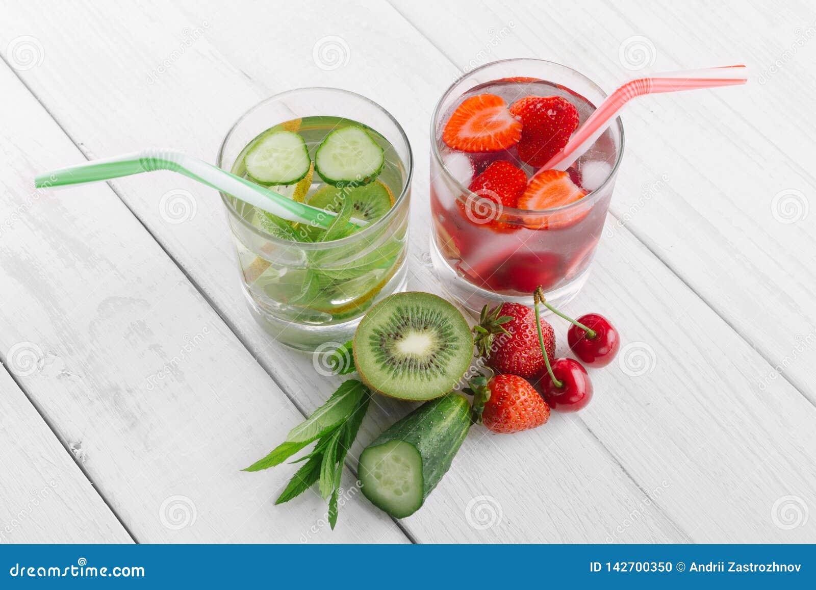 Kallt vatten i exponeringsglas, ny grön kiwi, mintkaramell och gurka, jordgubbar och körsbär Nya hemlagade vitaminer
