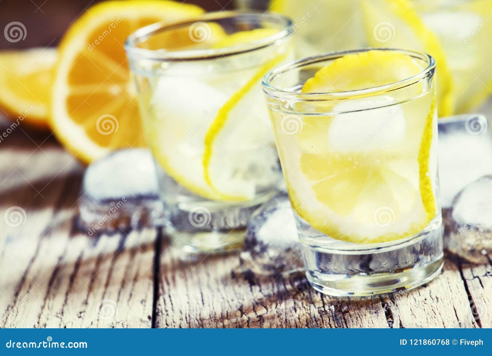 Kalter russischer Wodka mit Zitrone und Eis im Schnapsglas, Weinlese flehen an