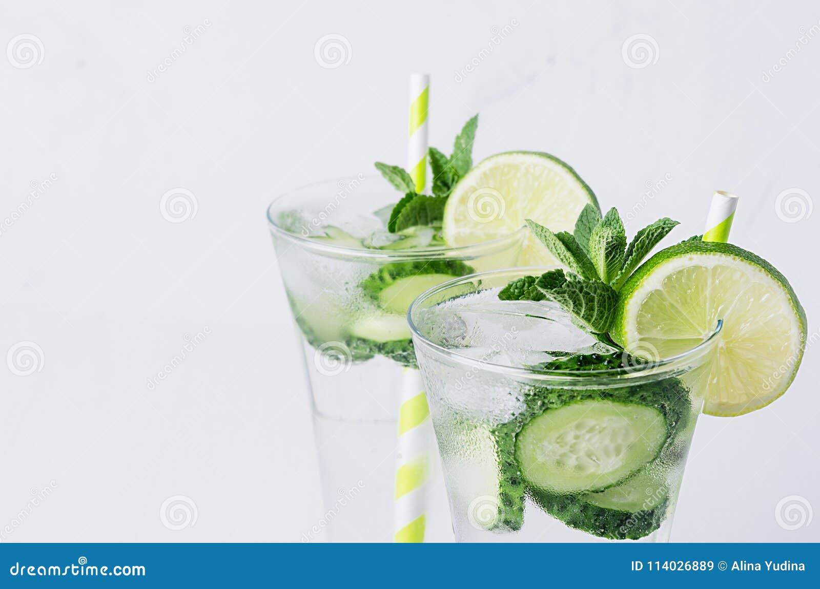 Kaltes transparentes Getränk des Sommers mit Eiswürfeln, Scheiben Kalk, Gurke, Stroh und Zweige prägen auf weißem hölzernem Brett