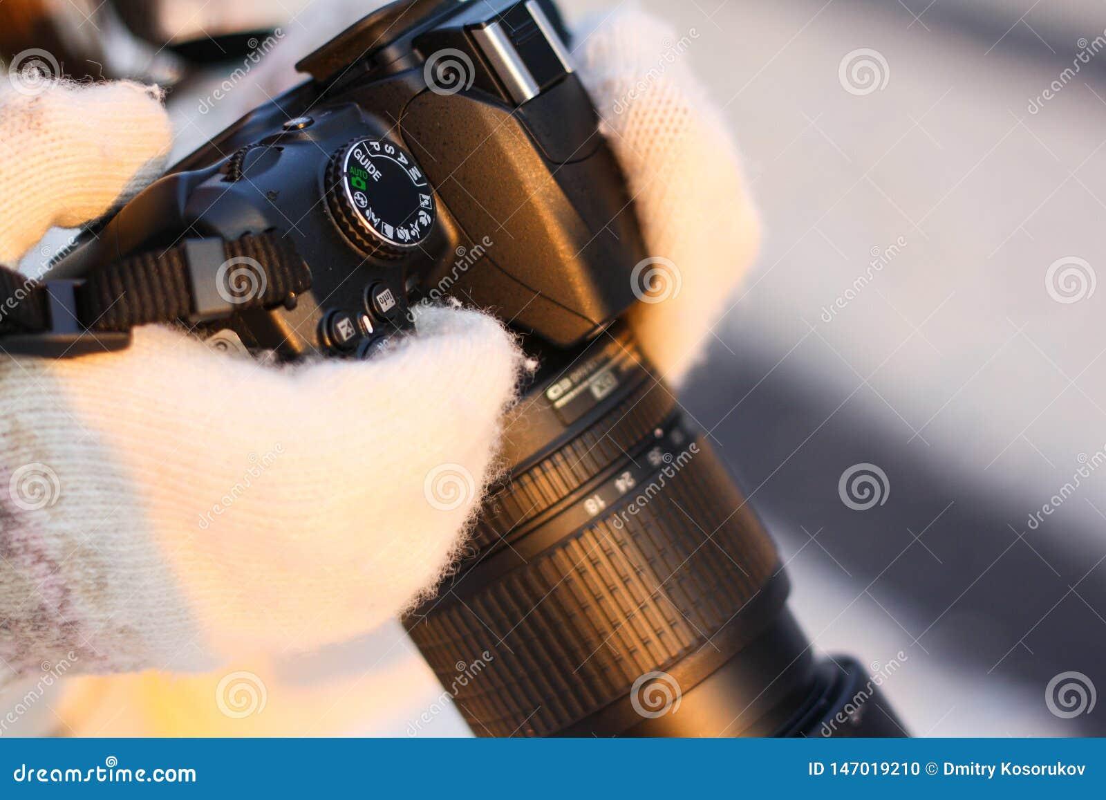 Kamera i händerna av en flicka i vinterskogen