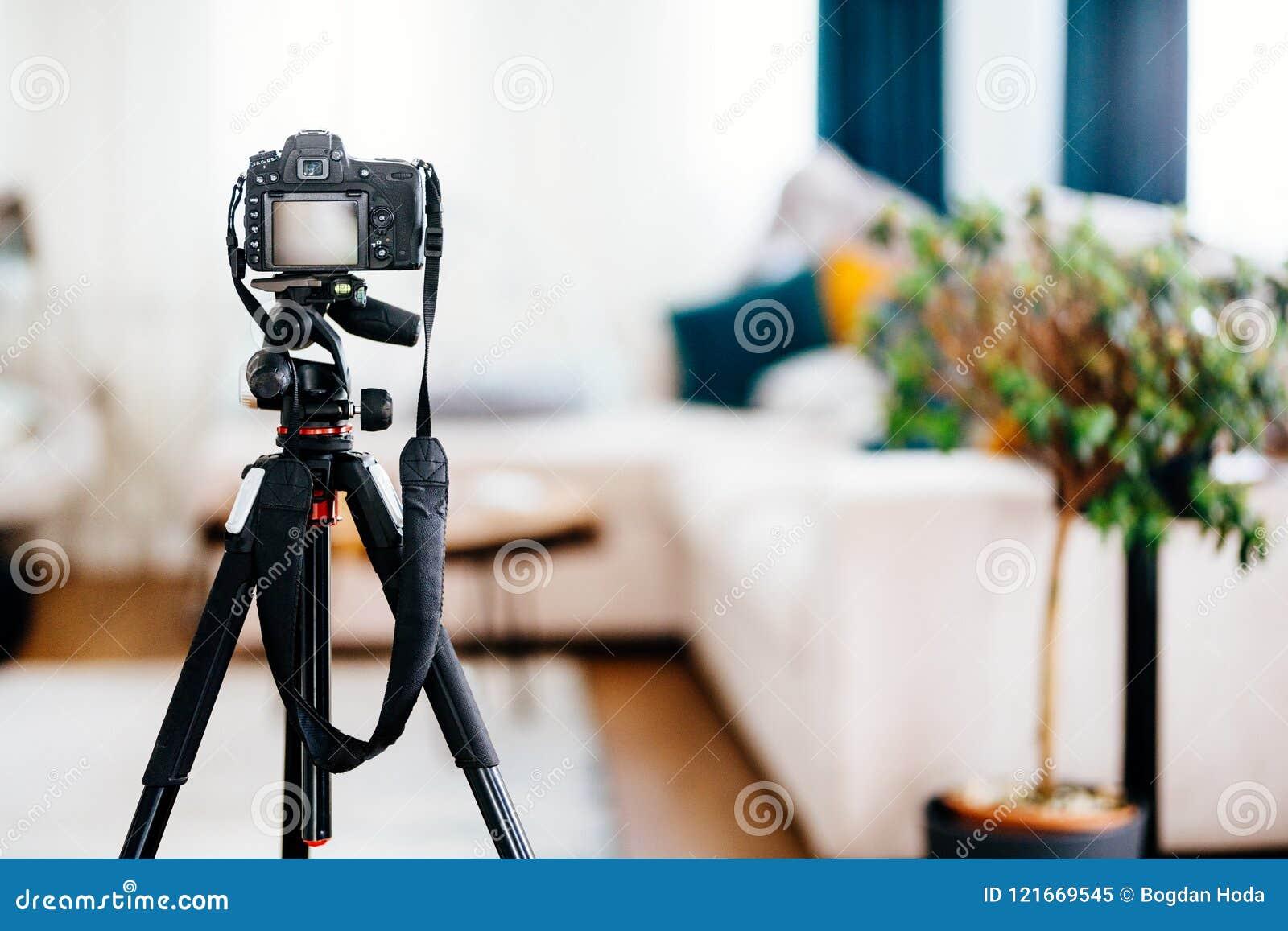 Kamera på tripoden som tar fotografier av inredesignen, möblemang och hus