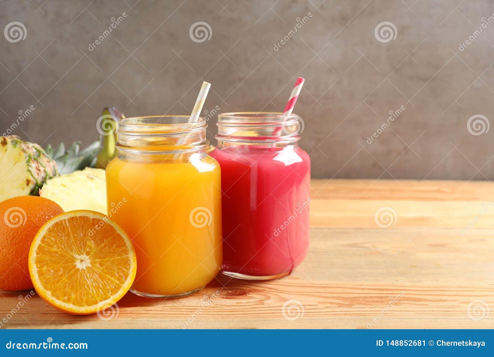Kamieniarz?w s?oje z r??nymi sokami i ?wie?ymi owoc na drewnianym stole przeciw koloru t?u