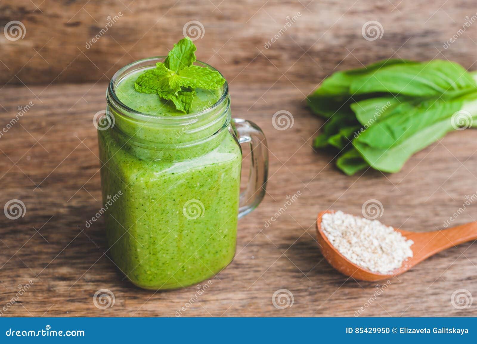 Kamieniarza słoju kubki wypełniali z zielonym szpinaka, banana i kokosowego mleka zdrowie smoothie z z łyżką oatmeal na drewniany