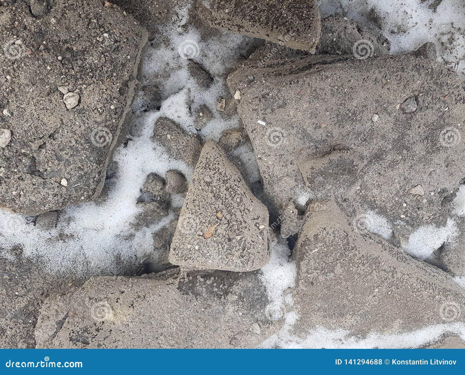 Kamienie granit na śnieżnej tło teksturze, śnieżni kamienie blisko góry rzeki, śnieżysta ziemia