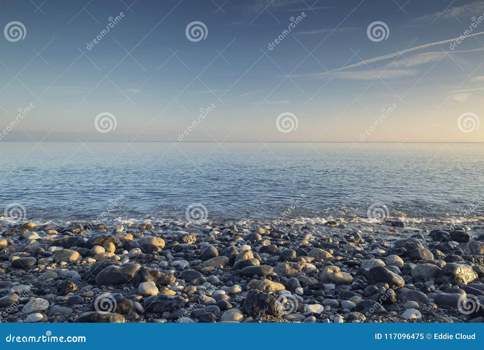 Kamienista plaża przy lato rankiem