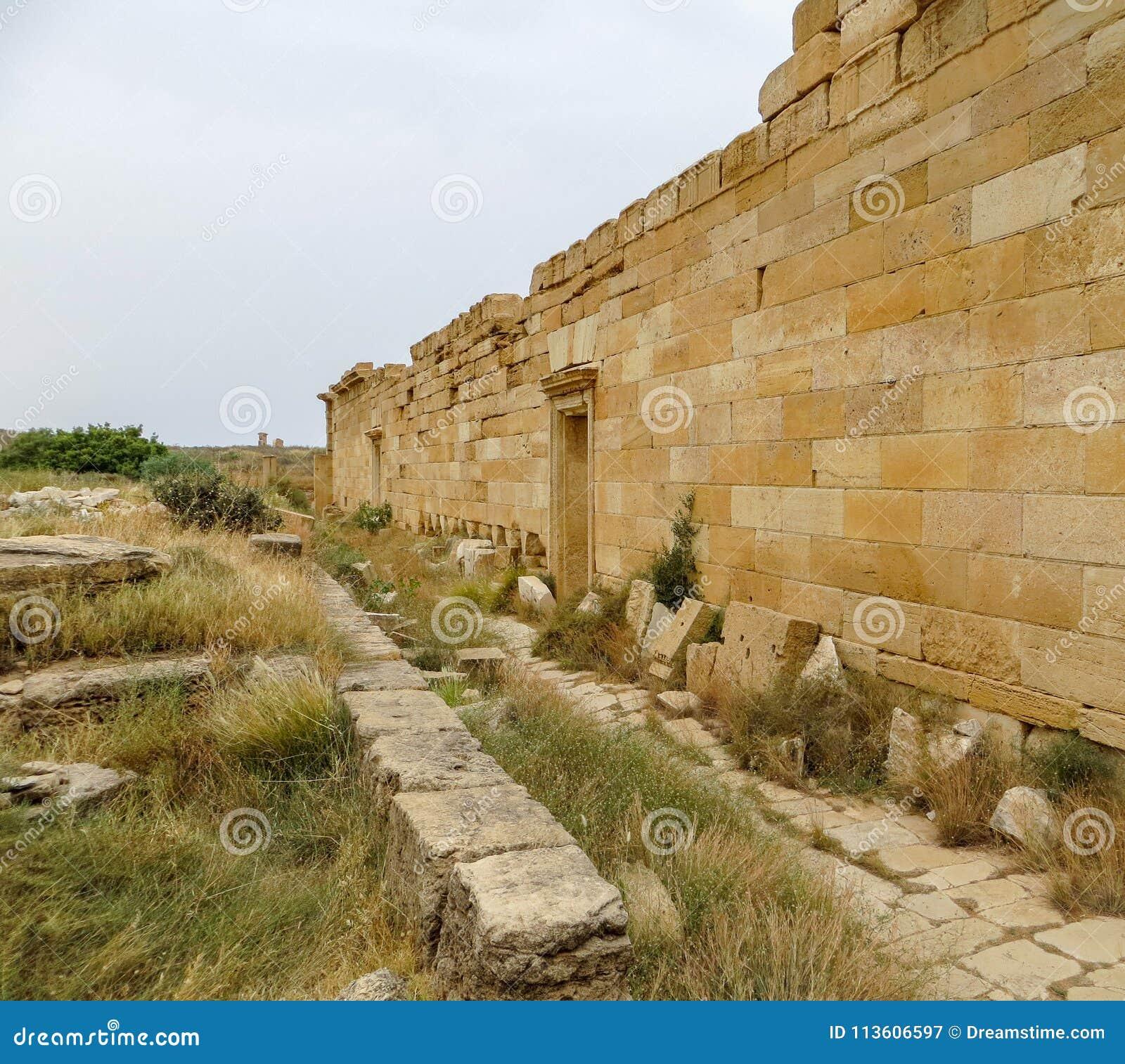 Kamienna ściana i bloki przy antycznymi Romańskimi ruinami Leptis Magna na Libia ` s Śródziemnomorskim wybrzeżu