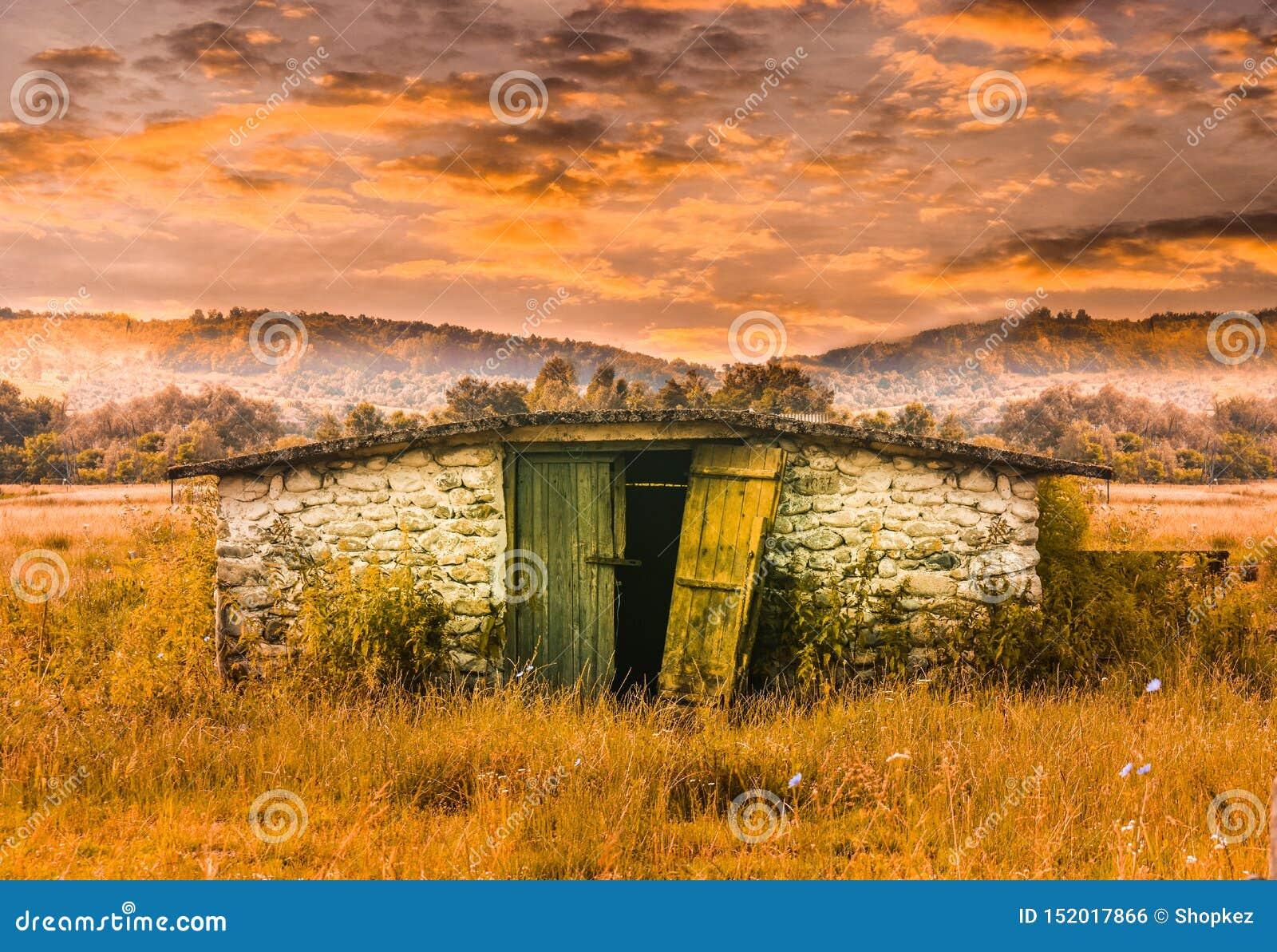 Kamienny stajnia budynek w trawy polu przy zmierzchem Zaniechana stara jata w bajki scenie Projektująca akcyjna fotografia z wsią