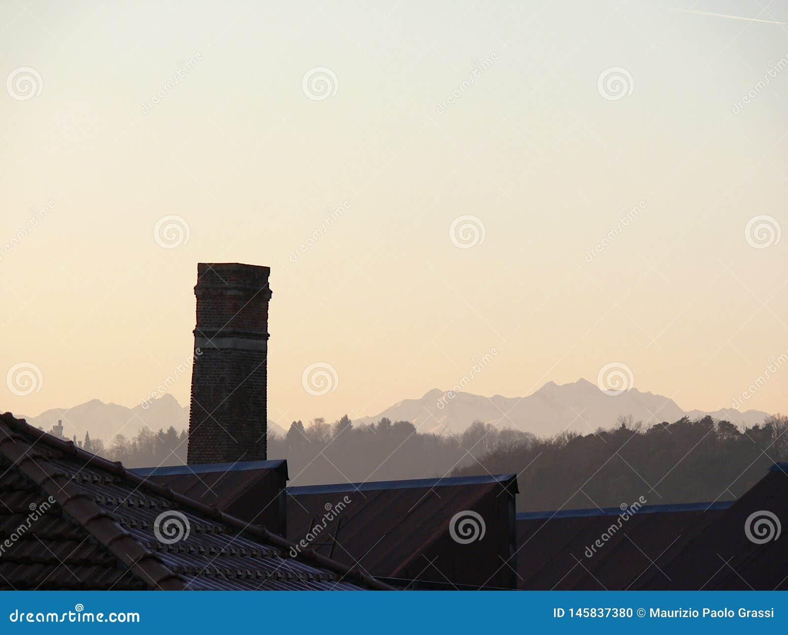 Kamin des alten verlassenen Industriegeländes Arbeit der Industriearchäologie Im Hintergrund das Profil der Bergalpen