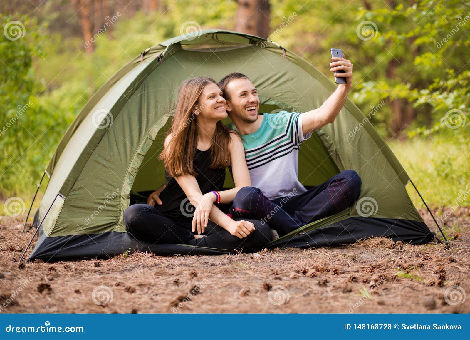 Kampierende Paare im Zelt, das selfie nimmt Gl?ckliche Freunde, die Spa? togheter haben Konzeptlebensstil und -technologie
