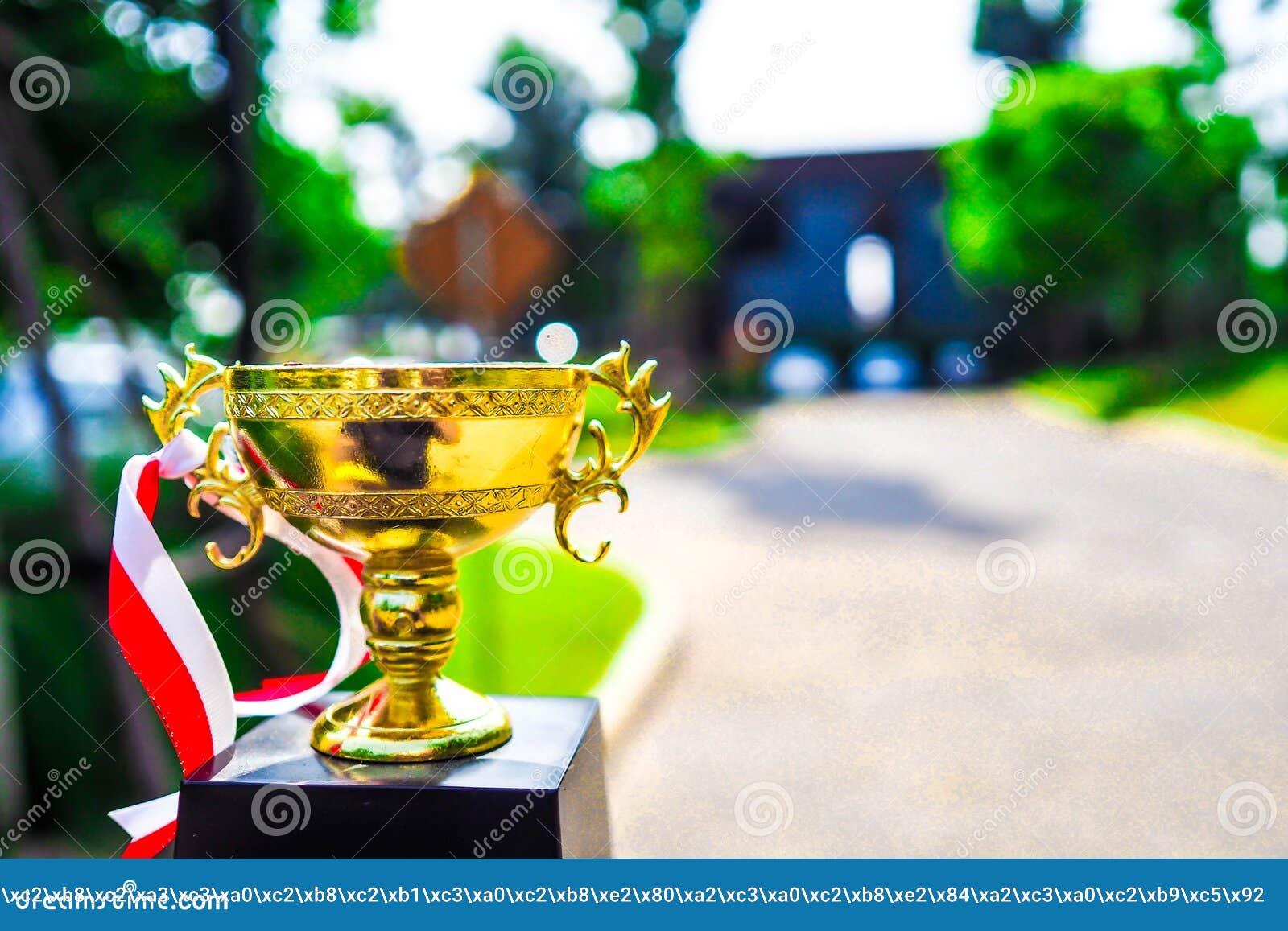 Kampioens gouden die trofee op weg met groen exemplaar wordt geplaatst als achtergrond